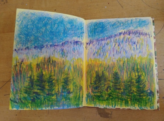 view of trees in front of foothills with blue, violet and green artist's crayons in tiny handmade sketchbook